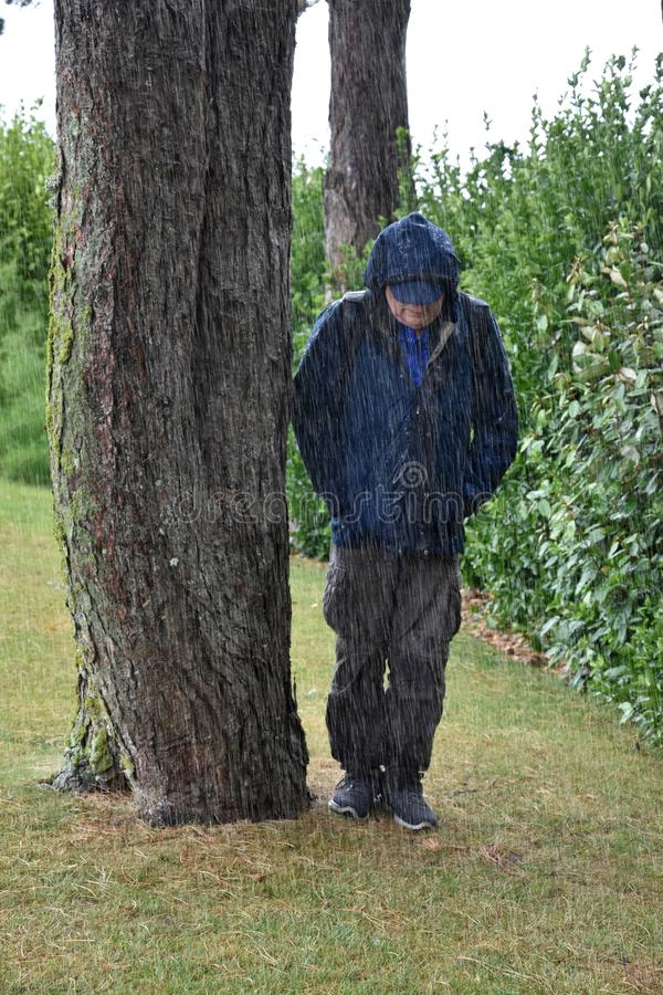 It rains cats and dogs, man seeks protection royalty free stock photography