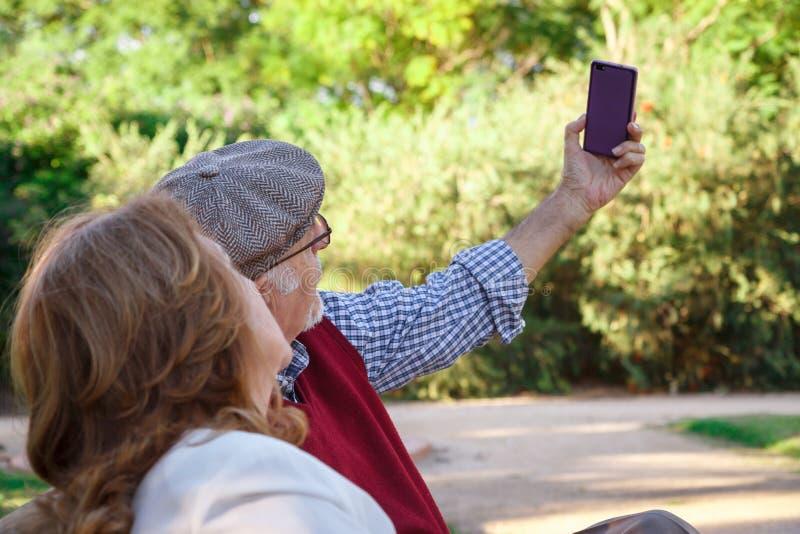 Senior man and senior woman doing a self-portrati royalty free stock photos