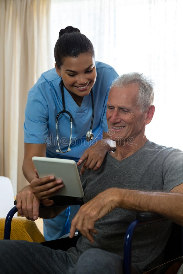 Senior man showing digital tablet to doctor in retirement home. Senior men showing digital tablet to female doctor in retirement home royalty free stock photos