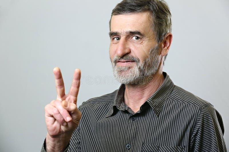 Senior man showing victory sign royalty free stock photos