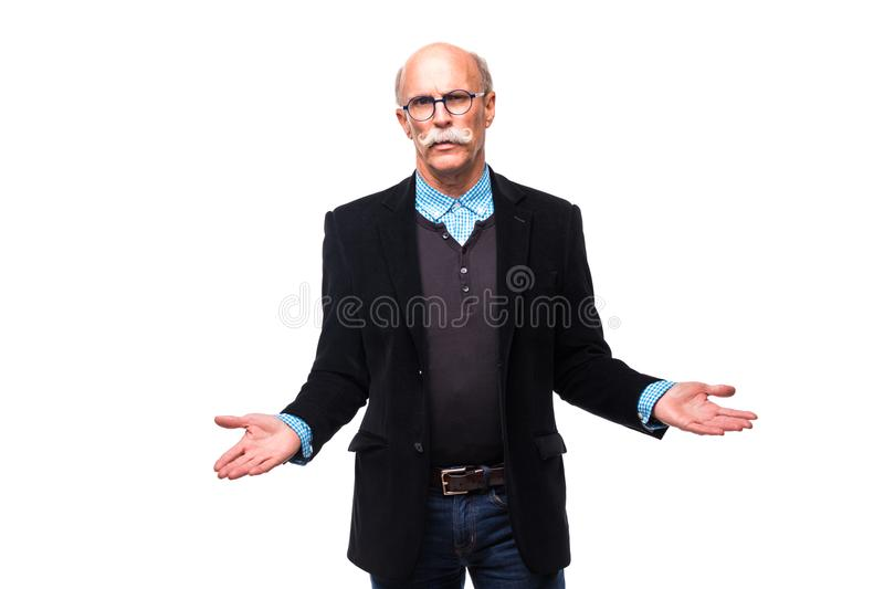 Senior man shrugging with raised hands on white background royalty free stock image