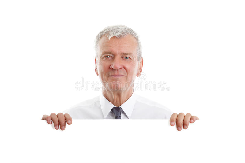Senior man with signboard. Portrait of senior businessman holding in hand a blank white signboard while standing against white background stock image