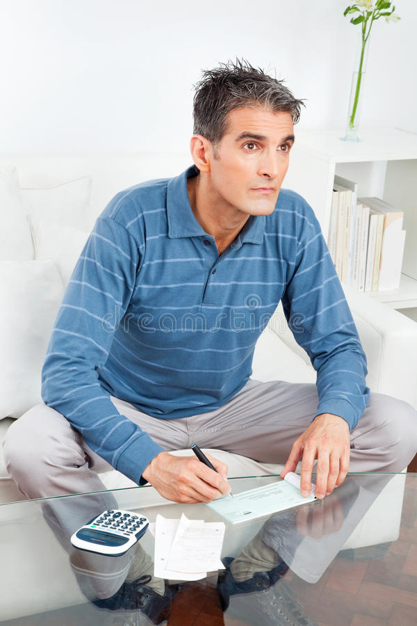 Senior man signing check. On living room table royalty free stock photos