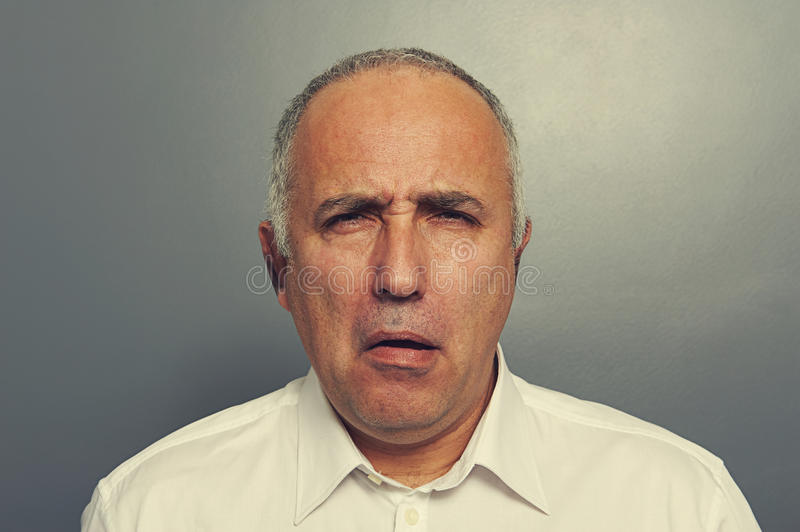 Senior man with silly expression. Portrait of senior man with silly expression on his face over grey background royalty free stock photos
