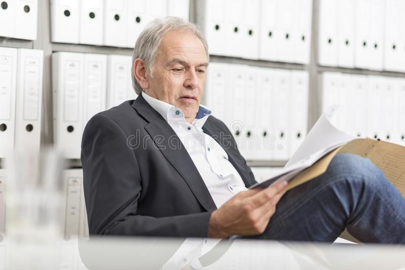 Senior man with sits at a desk, scrolling in a document file royalty free stock photos