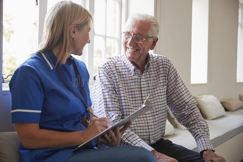 Senior man sits with nurse making notes at retirement home royalty free stock photography