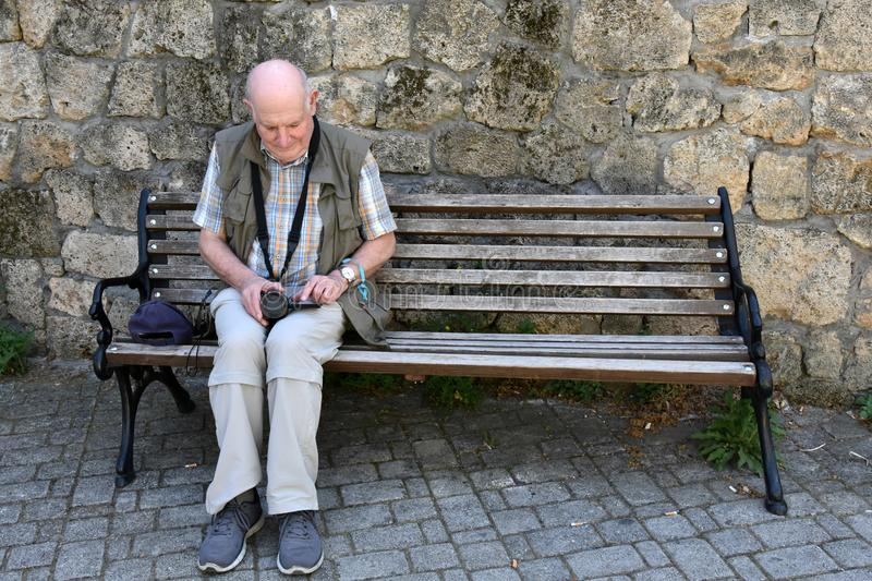 Senior man sits on a bench in front of natural stone masonry stock images
