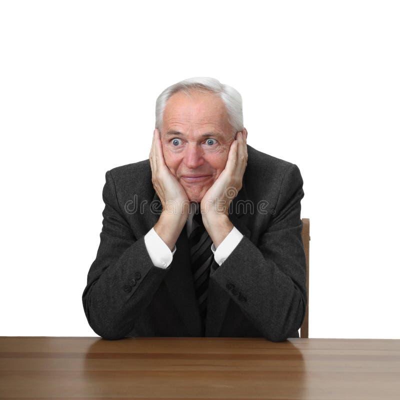 Senior man sits at table royalty free stock image