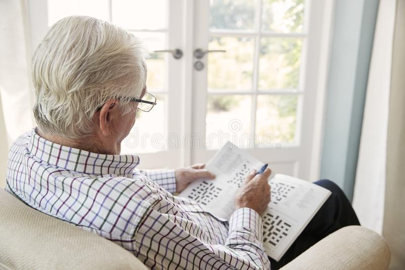 Senior man sitting in an armchair doing crossword, close up stock images