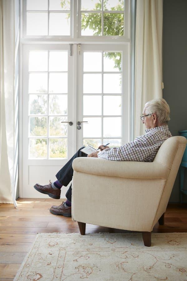 Senior man sitting in armchair doing crossword stock image