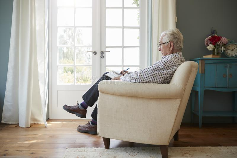 Senior man sitting in an armchair doing crossword, side view stock images