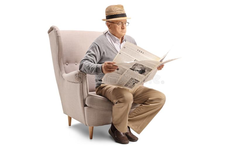 Senior man sitting in an armchair and reading a newspaper royalty free stock images