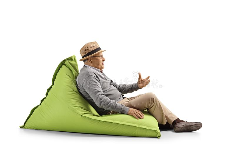 Senior man sitting on a bean-bag and gesturing with hand. Full length shot of a senior man sitting on a bean-bag and gesturing with hand  on white background stock photo