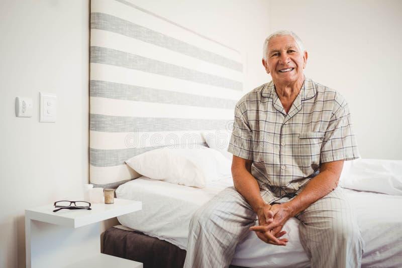 Senior man sitting on bed royalty free stock images