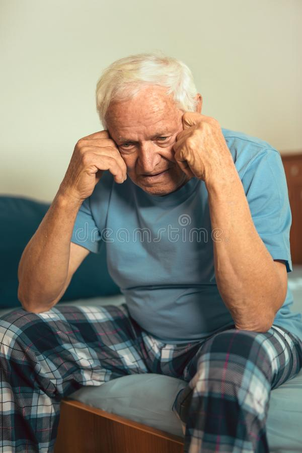 Senior Man Sitting On Bed Suffering From Depression stock image