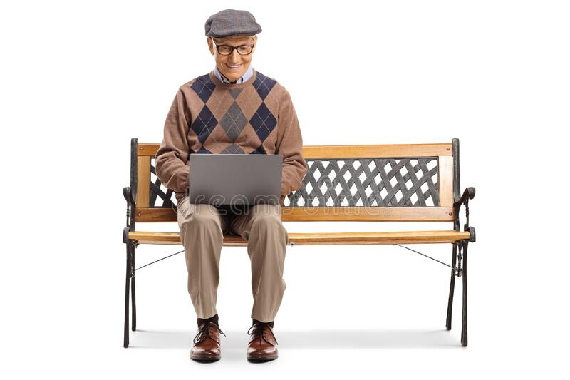 Senior man sitting on a bench and using a laptop computer stock image