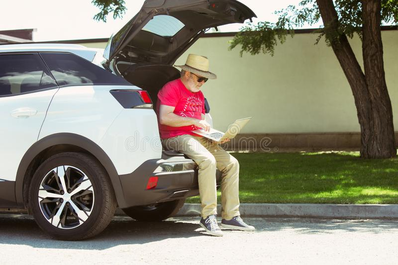 Senior man sitting on his car`s trunk and working outdoors. At the city`s street in sunny day. Male model in sunglasses using notebook. Concept of working stock images