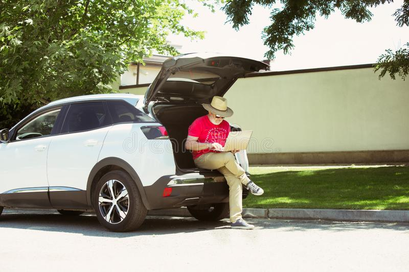 Senior man sitting on his car`s trunk and working outdoors. At the city`s street in sunny day. Male model in sunglasses using notebook. Concept of working stock photography