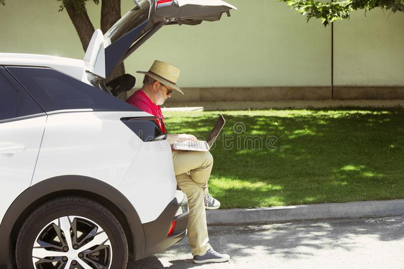Senior man sitting on his car`s trunk and working outdoors. At the city`s street in sunny day. Male model in sunglasses using notebook. Concept of working royalty free stock images