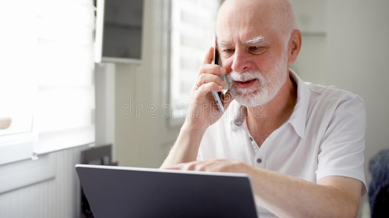 Senior man sitting at home with laptop and smartphone. Using cellphone discussing project on screen stock photo
