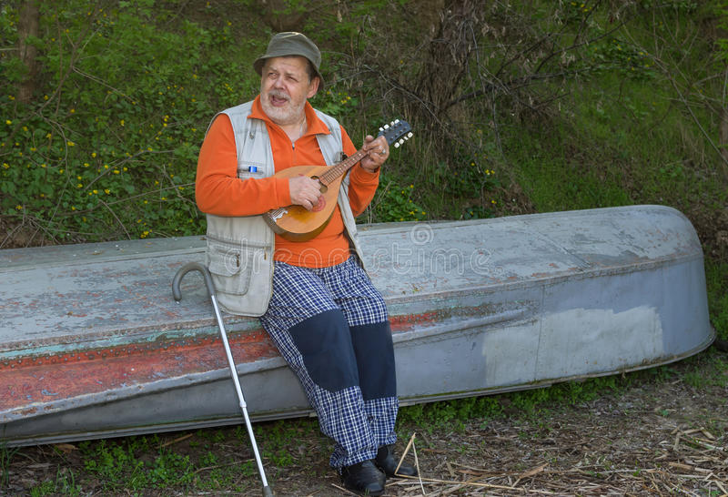 Senior man sitting on an old reversed boat and singing royalty free stock image