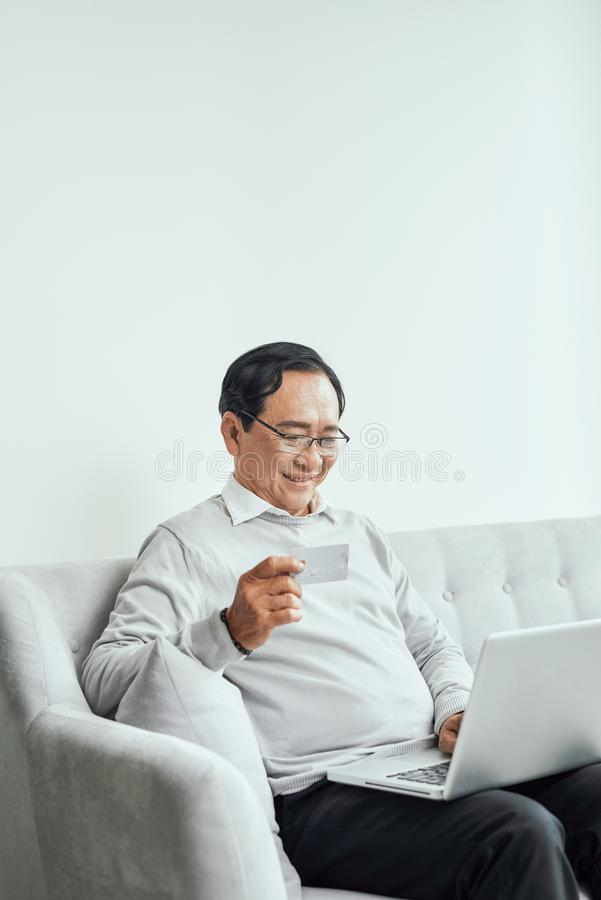 Senior man sitting in sofa and shopping online using laptop royalty free stock photography