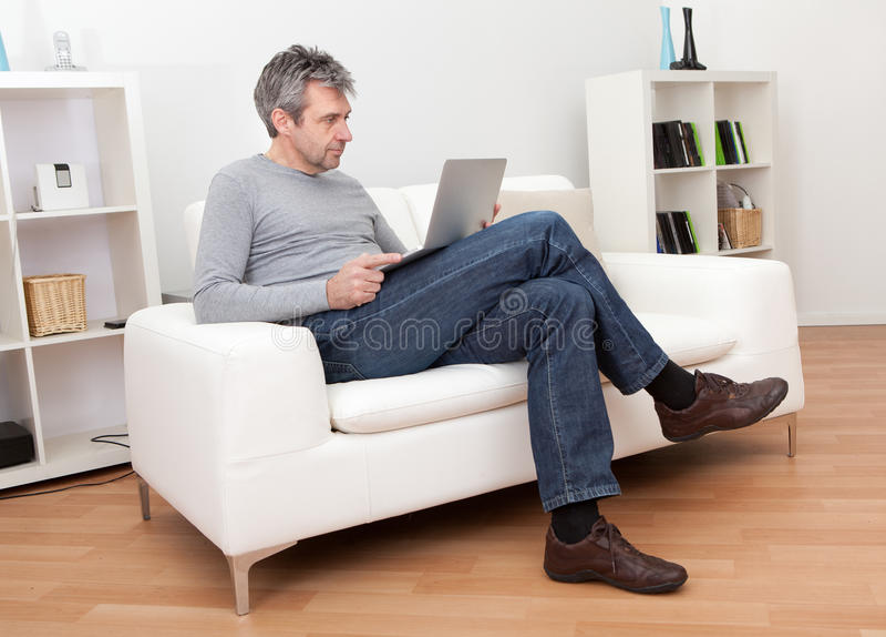 Download Senior Man Sitting In Sofa And Using Laptop Stock Photo - Image: 23927346