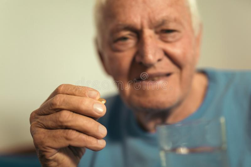 Senior man sitting taking medication royalty free stock photography
