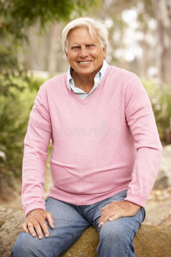 Senior Man Sitting On Wall stock photo