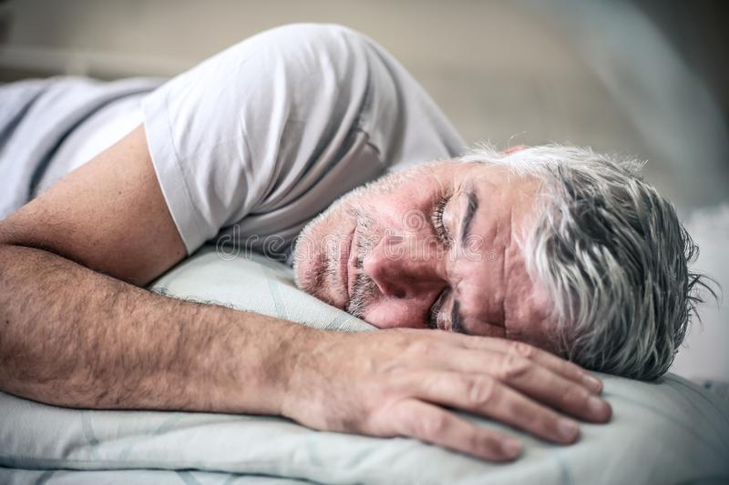 Sleepy senior man in bed. royalty free stock image