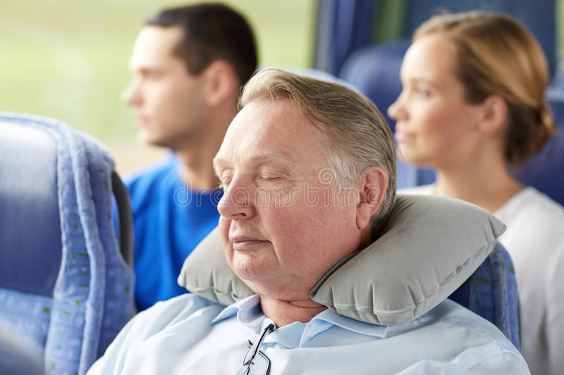 Senior man sleeping in travel bus with neck pillow stock images