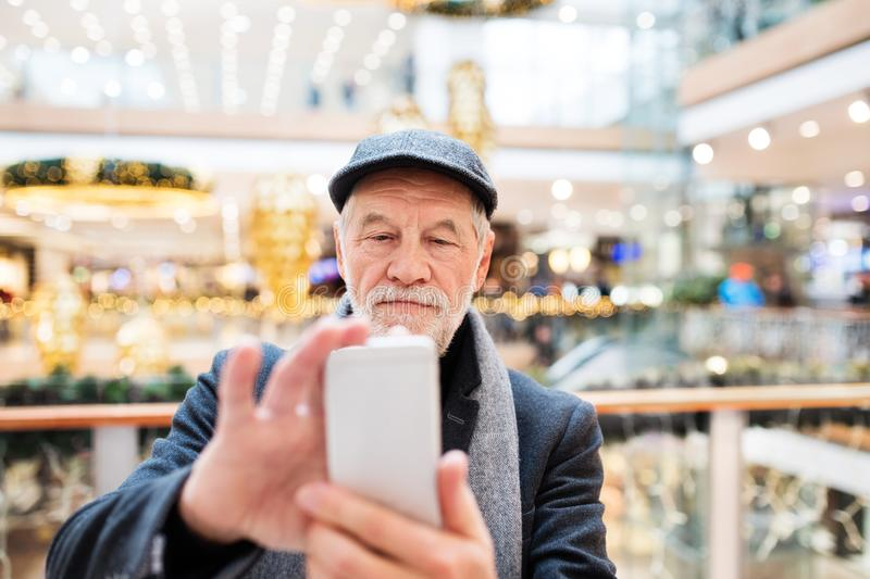 Senior man with smartphone doing Christmas shopping. stock photo