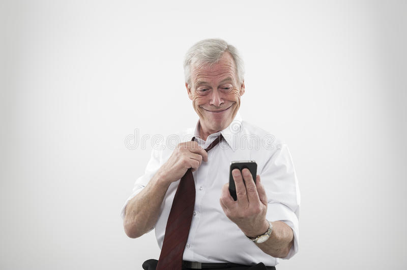 Senior man smiling at a mobile phone. Senior man relaxing and loosening his tie smiling with glee and anticipation as he looks at the caller ID or text message stock images