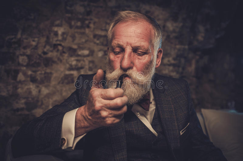 Senior man with a smoking pipe.  royalty free stock images