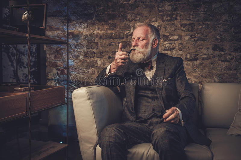 Senior man with a smoking pipe stock photography