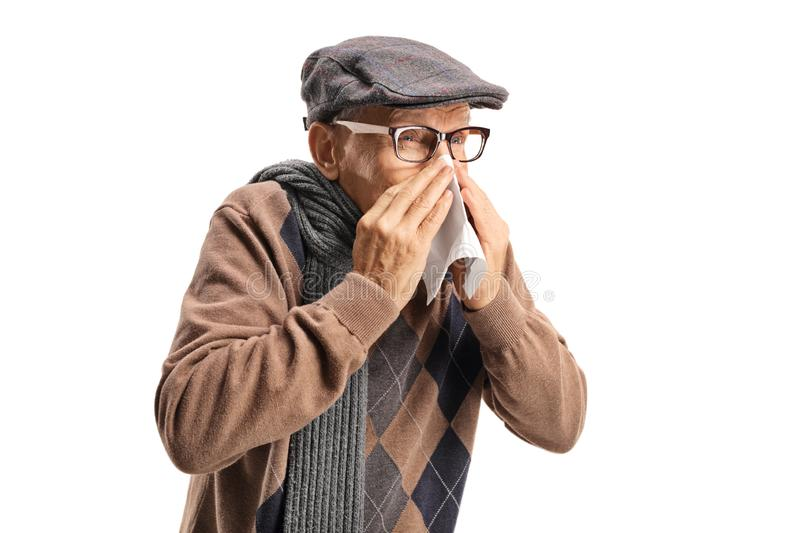 Senior man sneezing and wiping nose royalty free stock images