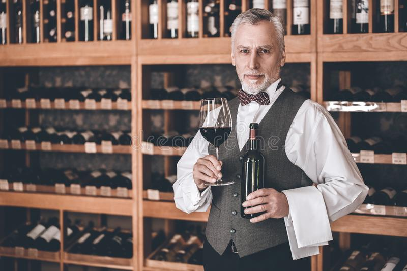 Sommelier Concept. Senior man standing with bottle and glass of wine smiling confident. Senior man sommelier standing near cabinet holding bottle and glass of stock photos