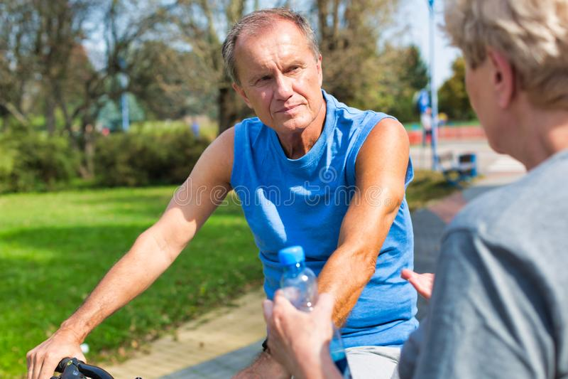 Senior man in sportswear talking to woman in park stock images