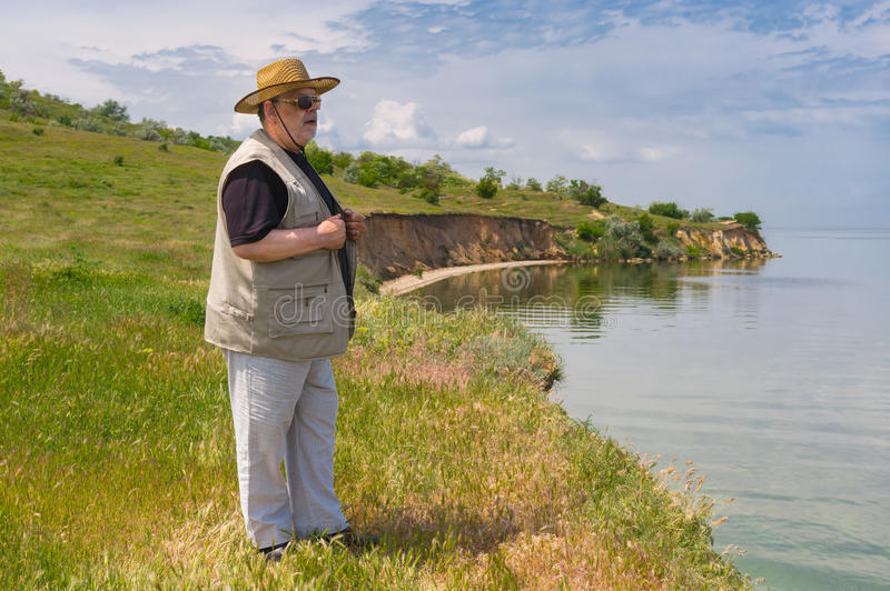 Senior man standing on abrupt riverside of the Dnepr river, Ukraine royalty free stock photos