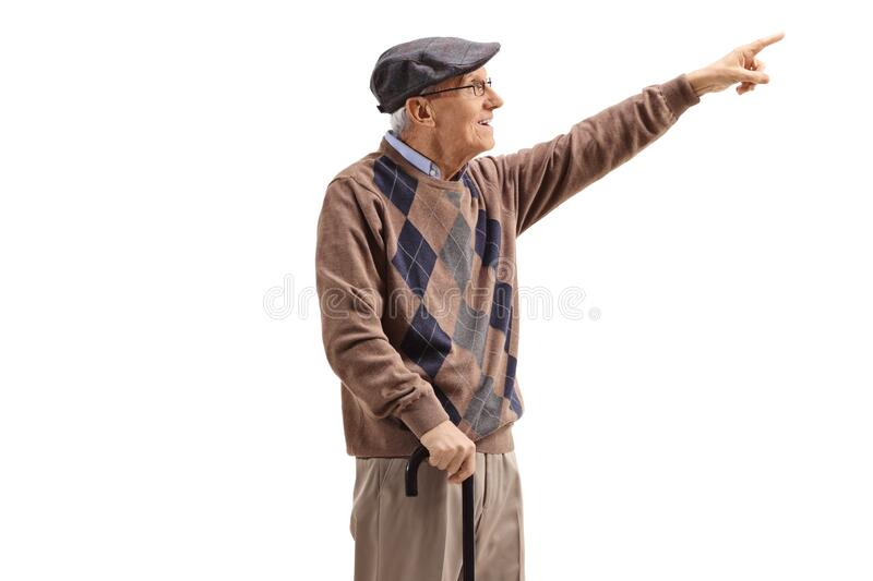 Senior man standing with a cane and pointing up in the distance royalty free stock photo