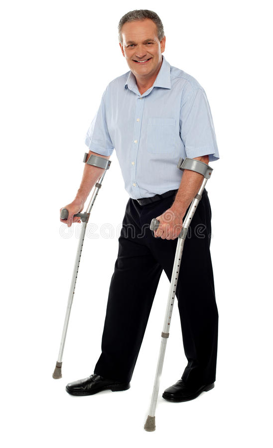 Senior man standing with the help of crutches stock photos