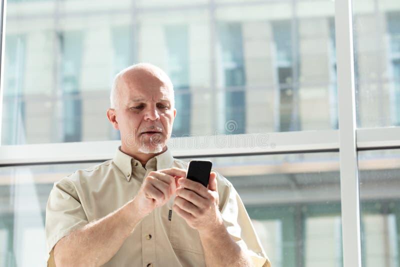 Senior man standing indoors in sunlight royalty free stock photos