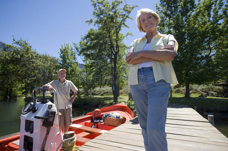 Senior man standing in moored motorboat, focus on wife standing on lake jetty, smiling, portrait royalty free stock image