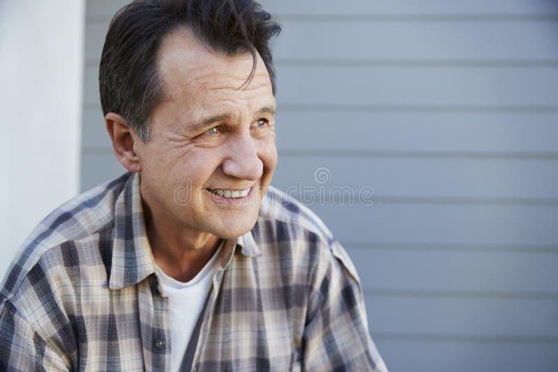 Senior Man Standing Outside Grey Clapboard House stock photo