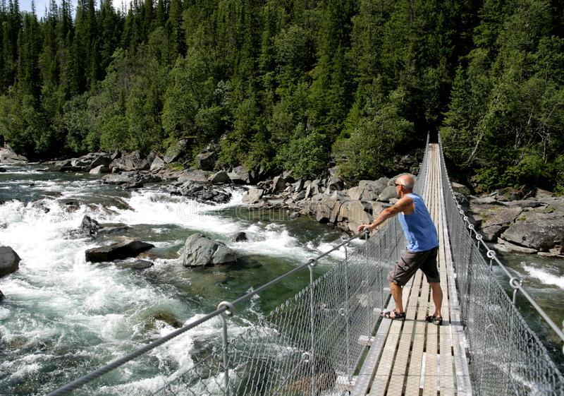 Man walking over a suspension bridge royalty free stock images