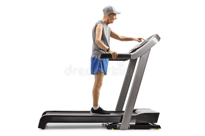 Senior man standing on a treadmill and pushing a button on display royalty free stock photography