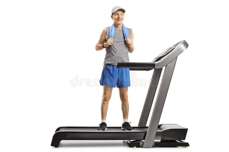 Senior man standing on a treadmill with a towel around his neck royalty free stock photo