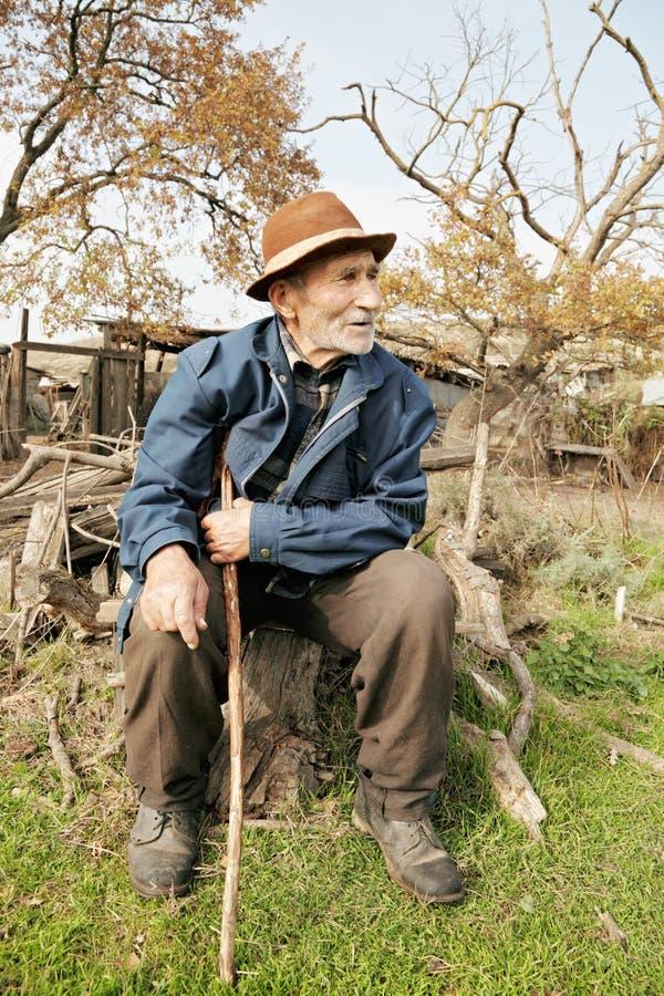 Senior man with stick. Sitting on stump outdoors stock photography