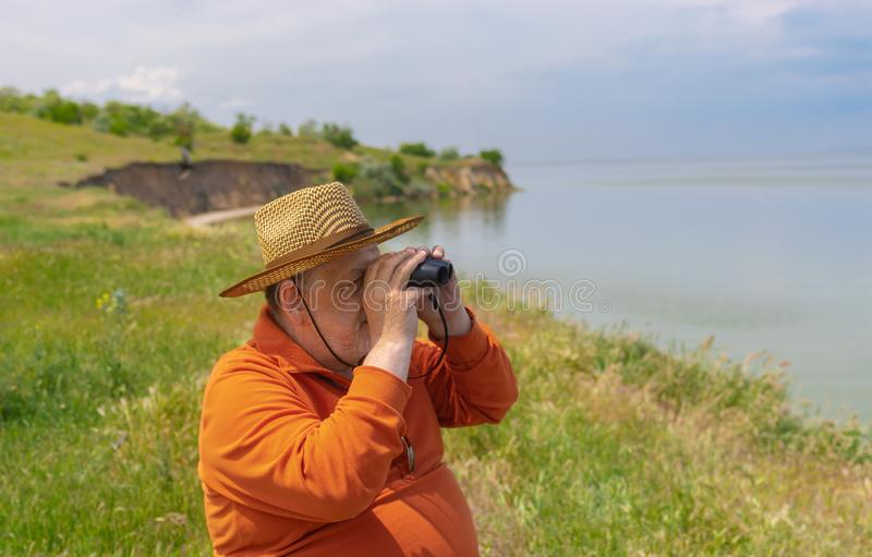 Senior man in straw hat looking into binocular while sitting on Dnipro riverside royalty free stock photos