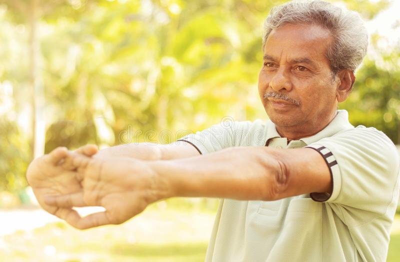 Senior man stretches hands before exercise - Concept of elderly person fitness outdoor - 60s person doing yoga asana at. Park royalty free stock images